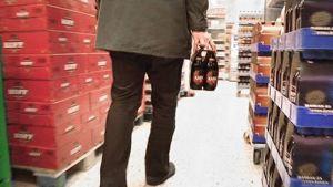 Mies kantaa olutta kaupassa.