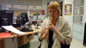 Kansanmusiikin lisensiaatti, läänintaiteilija Minna Raskinen kiertää luennoimassa vanhoista soittimista. Kuvan soitin on puusarvi.