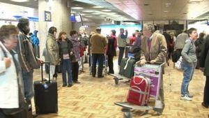 Matkustat odottavat matkalaukkujaan saapuvien lentojen hallissa Helsinki-Vantaan lentokentällä.