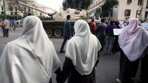 Egyptiläiset mielenosoittajat marssivat armeijan tankin vieressä  Tahirin aukiolla.