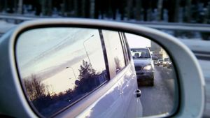 Liikenneruuhka heijastuu auton taustapeilistä.