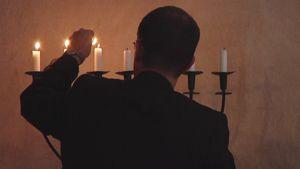 Mies sytyttää kynttilöitä