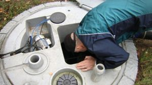 Mies ottaa vesinäytettä jätevesikaivosta.