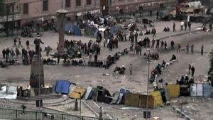 Kairolaisia milenosoittajia seisoskelemassa aamuhämärässä risteyksessä