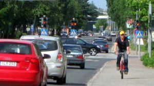 Autoja ja pyöräilijä kadulla, jonka liikennevalot vilkuttavat keltaista.