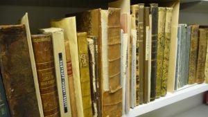 Vanhoja kirjoja kirjahyllyssä.