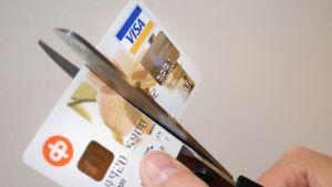 Visakorttia leikataan halki.