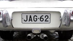 Kadun viereen parkkeeratussa valkoisessa autossa on rekisterikilpi JAG-62. Jaguarissa on erikoisenmallinen pakoputki, joka sijaitsee aivan rekisterikilven alla.