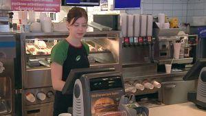 Nuori nainen hampurilaisbaarin kassalla