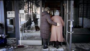 Hoitaja auttaa vanhusta kävelemään sisälle hoitokotiin.