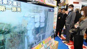 Kansalaiset katsovat suurikokoista televisiota tokiolaisessa kaupassa.