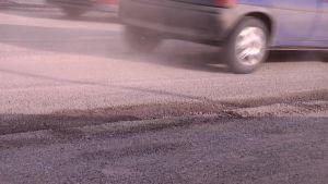Liikenteen nostattamaa katupölyä keväällä. Tien piennar ja hiekoitussoraa.