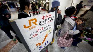 Tokiolaisia jonossa juna-asemalla.