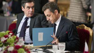 Ranskan pääministeri Francois Fillon istuu papereitaan seleilevan presidentti Nicolas Sarkozyn vasemmalla puolella.