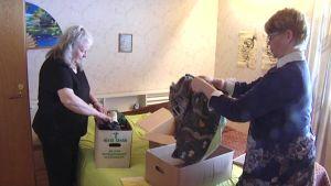 Marja Jääskeläinen ja Sirpa Rivinoja lajittelevat kierrätykseen meneviä vaatteita.