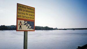 Heikoista jäistä varoittava merkki rannassa.