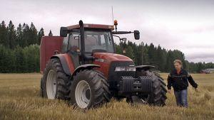 Maanviljelijä traktorinsa vieressä puidulla pellolla