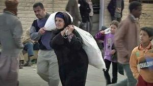 Mies ja nainen kantavat raskaita  säkkejä