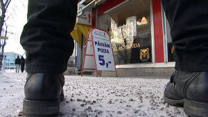 Pitserian ulkopuolella olevassa mainosständissä mainostetaan viiden euron pitsaa.