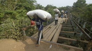 Ihmiset kantavat kaakaosäkkejä sillalla.