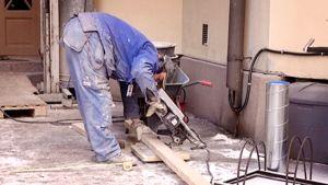 Remonttimies leikkaa pyörösahalla lankkua kerrostalon pihalla.