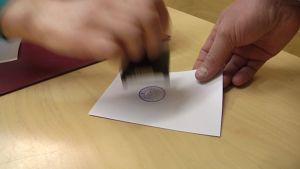 Kuvassa vaalivirkailija leimaa äänestyslippua