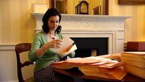 Nainen laittaakutsuja kirjekuoriin