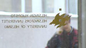 Henkilö kuvattuna yliopiston lasioven läpi.