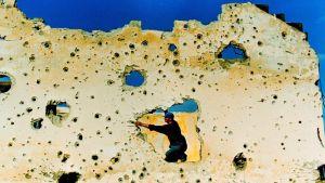 Mies kyykkii raunioituneen rakennuksen seinään revenneessä aukossa ja tutkii seinää kädellään.