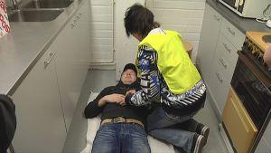 Kilpailija tarkistaa pyörtyneen miehen elintoimintoja.