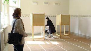 Vanha nainen menossa äänestyskoppiin.