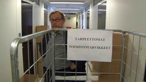 Vihreiden kansanedustaja Erkki Pulliainen seisoo tyhjän toimistotarvikekärryn takana.