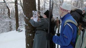 Mies kiinnittää kuvaa puuhun.