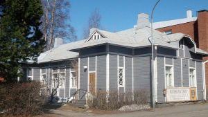 Vanha puutalo kerrostalojen lomassa Joensuun keskustassa.