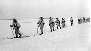 Lumipukuiset sotilaat hiihtävät järven jäällä talvisodassa.