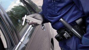Poliisi tutkii alkometria auton  vieressä.