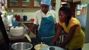 Kaksi naista laittaa ruokaa keittiössä.