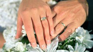 Miehen ja naiset kädet sormuksien kera