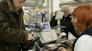 Moni virolainen suunnittelee lähtevänsä töihin ulkomaille huonon työllisyystilanteen takia. Kuva kaupan kassalta Tallinnassa.