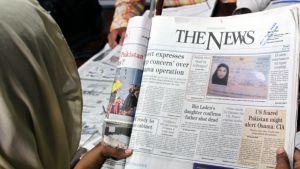 Pakistanilainen nainen tutkii torstaina sanomalehdessä julkaistua kuvaa Osama bin Ladenin vaimon  Amal Ahmed al-Sadahin passista.