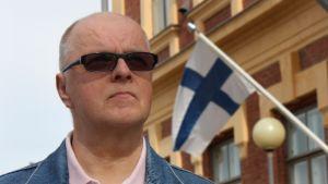 Osmo Kokko ja Taidemuseon seinässä liehuva Suomen lippu.