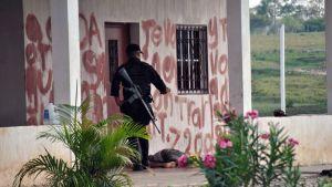 Sotilas seisoo talon kuistilla, jossa makaa ruumis.