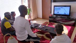 Tummaihoiset miehet katsovat Suomen jääkiekko-ottelua.