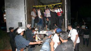 Meksikon poliisi siirtää laittomia siirtolaisia ulos rekan tavaratilasta.