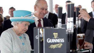 Elisabet II katselee Guinness-tuopin kaatoa.