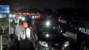 Poliisiautoja ja punaisin valoin vilkkuvia ambulansseja Karachin yössä.
