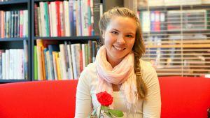 Abiturienttien ruotsin kielen kirjoituskilpailun voittaja Emilia Korhonen hymyilee ruusu kädessään.