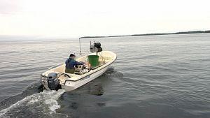 Kalastaja ajaa venettä Inarijärvellä.
