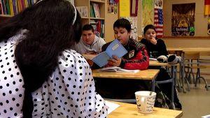 Romaninainen opettaa koulussa romanikieltä lapsille.