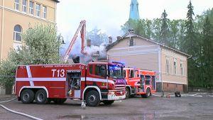 Aleksanterin koulun puurakennuksen paloa sammutetaan